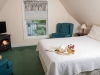 King bed with white bedspread, green carpet, two blue wing back chairs and all season fireplace with tb