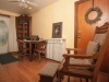 Sitting area, hardwood floors table and chairs with laptop, and old fashion wood chair with ottoman