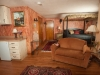 Room with canopy bed, dark bedspread, Kitchenette area with refrig and sink, room done in peach color and hardwood floor
