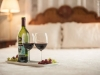Wine bottle with two wine glass with red wine on a tray on the bed