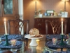 Dining table set up for Breakfast with blue paisley placemats, with white pedestal with banana nut bread