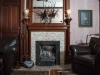 LIving room with Gas fireplace with tile around then hand carved mantel and outline