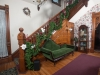 Foyer with Green love seat  grand staircase with carved wood and hardwood floors