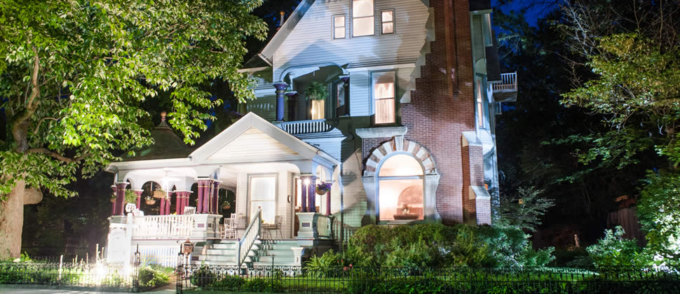 Historic 1892 Queen Anne Victorian inn with up lighting at night gorgeous front porch