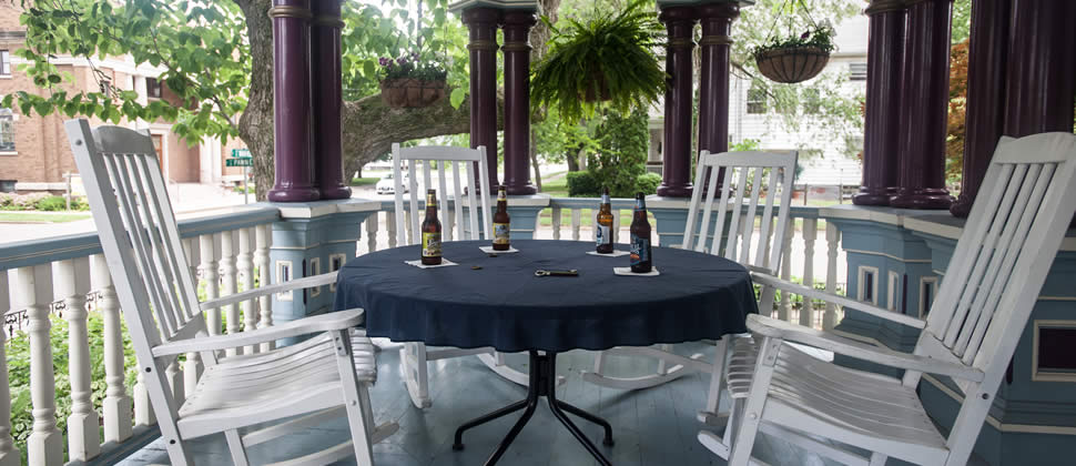 Table on the porch with 4 white rocking chairs, and 4 bottles of beer sitting on table