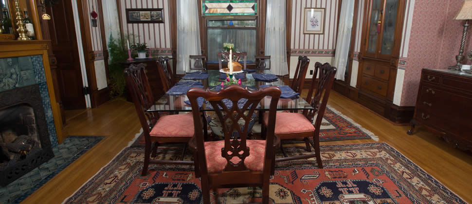 dining room with glass table and 6 victorian chairs, striped wall paper with gas fireplace